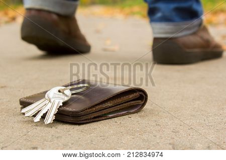 Man lost his keys and a purse with money. The men leave and only the legs and shoes are not in focus and the keys and wallet on the ground
