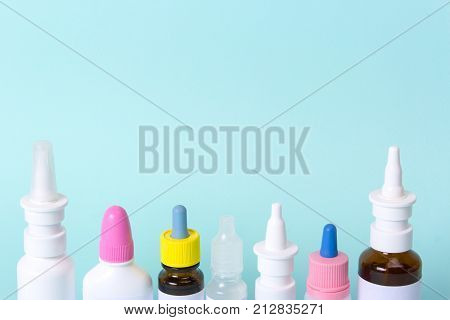 Nasal drops and a nose spray for the treatment of a common cold. Bottles and vials of medicines on a green background. What treatment to choose? Copy space for text