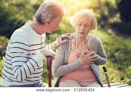 Heart attack. Unhappy sad aged woman sitting on the bench and holding her chest while having a heart attack