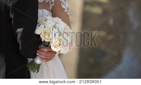 Elegant bride and groom posing together outdoors on a wedding day. Bride holding a white rose bouquet while standing next to groom. bride in a dress standing in a green garden and holding a wedding bouquet of flowers and greenery