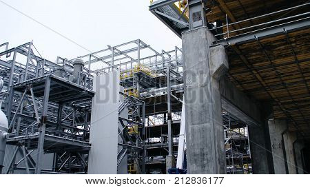 Metal construction of the future plant. Industrial zone, The equipment of oil refining, Close-up of industrial pipelines of an oil-refinery plant, Detail of oil pipeline with valves in large oil refinery.
