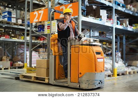 Young lift operator preparing products for shipment