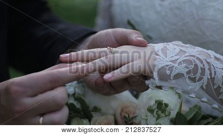 Bride wear ring on groom's finger. The groom puts the wedding ring to finger of the bride. marriage hands with rings. birde wears the ring on the finger of the groom HD