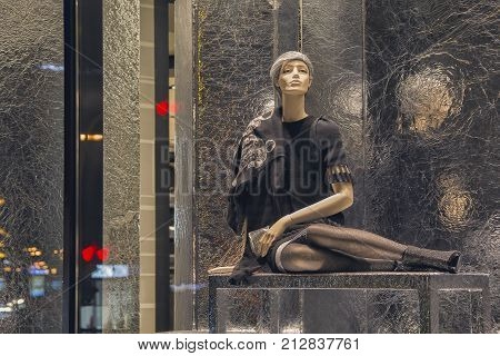 Female mannequin in shop window and reflecting city