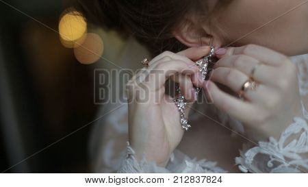 Beautiful bride in puts on earring. Beauty model girl is wearing jewelry for marriage. Wedding female portrait. Woman with curly hair and lace veil. jewelry and beauty concept - close up of beautiful woman wearing shiny diamond earrings HD