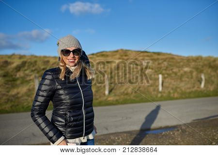 Trendy woman wearing a leather jacket woollen cap and sunglasses standing on a rural road in evening light with copy space smiling at the camera