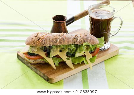 sandwich and black coffee on wooden board
