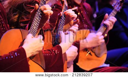 Women playing music with balalaika on concert. Russian instrument. Women play the balalaika.