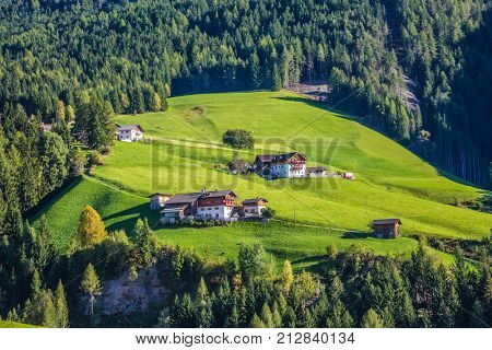 Rural pastoral in the Val de Funes, Dolomites. Warm autumn day. Charming chalet on a green grassy slope of the mountain. The concept of ecological tourism
