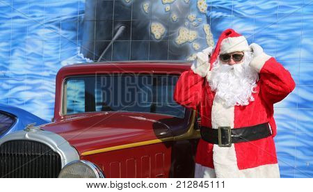 Santa Claus poses for his portrait with his car. Santa Claus gets ready for Christmas. Santa Claus on vacation.