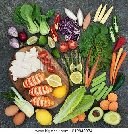 Diet health food concept with high protein meat and fish, vegetables, fruit, and dairy. Super food high in omega 3, antioxidants, anthocyanins, vitamins and fibre. Rustic background, top view.