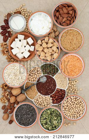 Health food for vegans with tofu, legumes, nuts, seeds, cereals, soya yoghurt, milk and chunks with foods high in fiber, antioxidants, vitamins and minerals on hemp paper background.