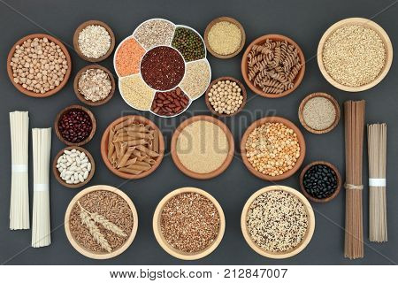 Healthy dried macrobiotic food with soba and udon noodles, pulses, cereals, whole wheat pasta, seeds and cereals, high in protein, omega 3,  antioxidants  and vitamins on rustic background,
