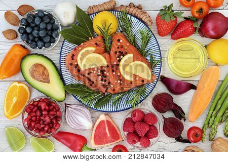 Nutrition for a healthy heart concept with fresh salmon, fruit, vegetables, nuts, herbs, spice and olive oil. Food very high in omega 3 fatty acids, antioxidants, anthocyanins, mineral and vitamins.