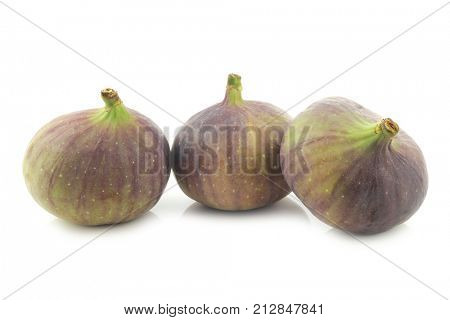 three figs (Ficus carica) on a white background