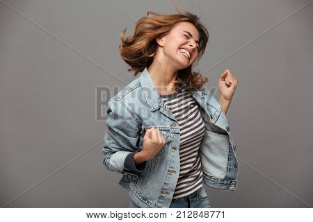 Portrait of a satisfied cheerful teenage girl dressed in denim jacket celebrating success while dancing isolated over gray background