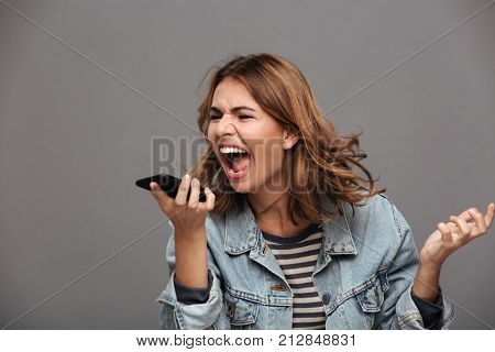 Portrait of a furious mad teenage girl dressed in denim jacket yelling at mobile phone isolated over gray background