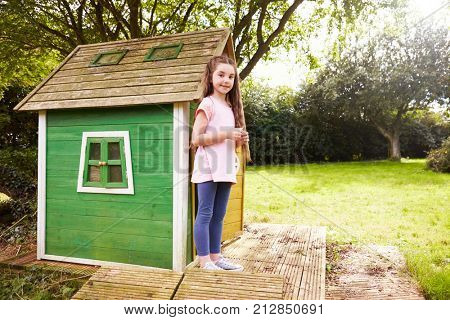 Portrait Of Girl Standing In Garden Next To Playhouse