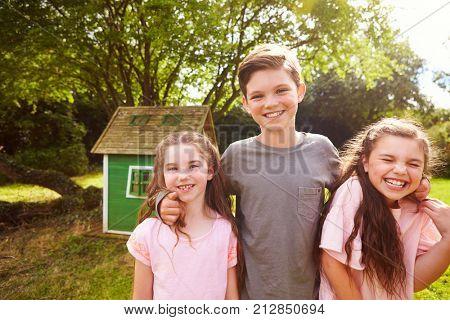 Portrait Of Children Standing In Garden Next To Playhouse