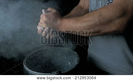 Talc sports. Closeup of a muscular man ready to workout. male powerlifter hand in talc and sports wristbands preparing to bench press.