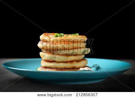 Plate with Hanukkah potato pancakes on table