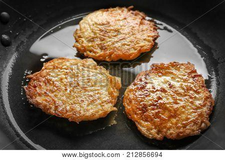 Frying pan with Hanukkah potato pancakes, closeup