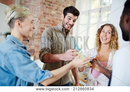 Ecstatic friends cheering with cocktails at home party and enjoying being together