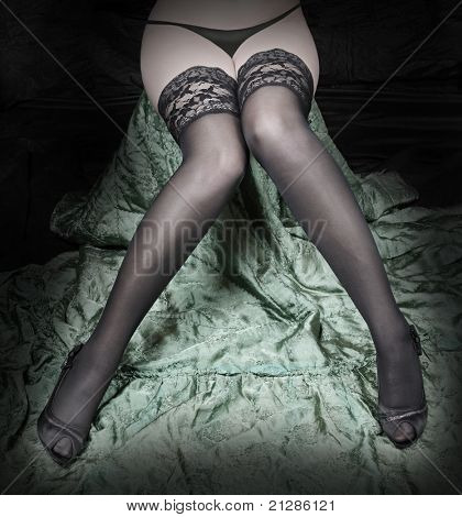 Low key photography of beautiful slim legs in black nylons on a green background.