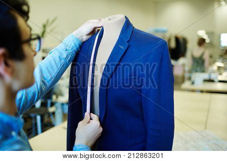 Self-employed tailor taking measures from jacket on dummy in his workshop