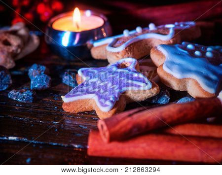 Gingerbread Christmas and cinnamon stick and star cookies are on wooden table and burning candles. Xmas still life object.