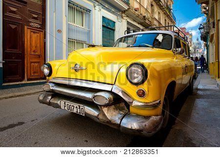 HAVANA,CUBA - NOVEMBER 6, 2017 : Urban scene with old classic american car on a narrow street in Old Havana