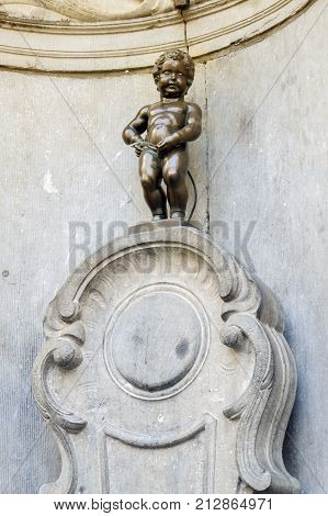 Brussels, Belgium - April 2015: Manneken Pis or Little Man Pee a landmark small bronze sculpture designed by Hiëronymus Duquesnoy the Elder located near Grand Place in the city of Brussels Belgium
