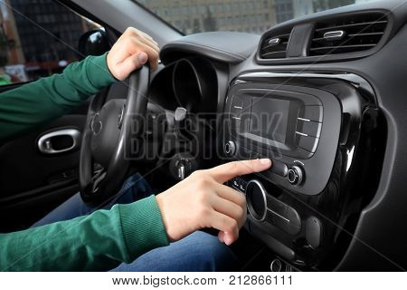 Man tuning radio in car