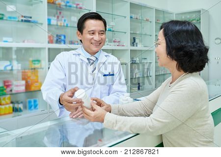 Professional Vietnamese pharmacist telling benefits of new medicine to the customer