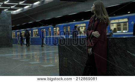 Young girl listens to music in headphones in the subway tunnel. Young female student listening to music in big headphones in the subway tunnel.