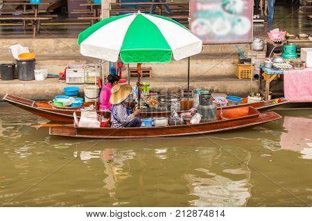 Old asians woman making thai noodle food at Damnoen Saduak floating market in Ratchaburi near Bangkok Thailand