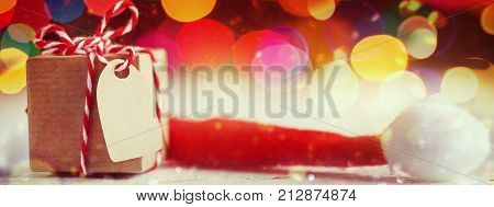 Christmas present or box for secret santa on colorful bokeh background. Banner.