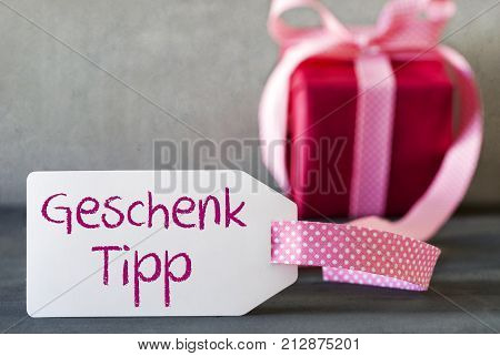 Label With German Text Geschenk Tipp Means Gift Tip. Pink Gift Or Present With Gray Cement Background