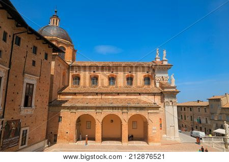 Urbino, Italy - August 9, 2017: The Cathedral. Piazza Duca Federico. Sculpture And Statue In Archite