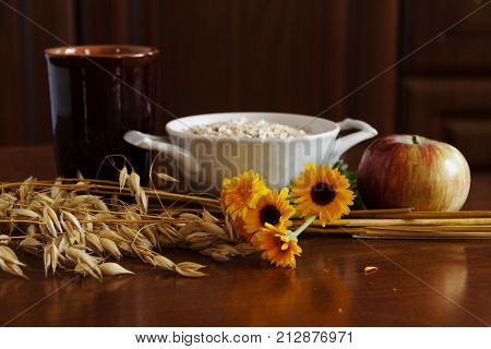 Oat Ears Stems And Oat Flakes In A White Pot, Marigold Flowers And Cup Of Milk And Apple On Dark Bro