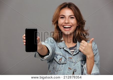 Close up portrait of a happy cheery teenage girl dressed in denim jacket holding blank screen mobile phone and showing thumbs up gesture isolated over gray background