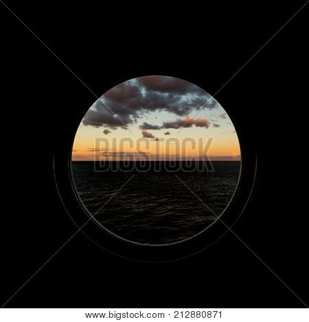 View Through Porthole On Dawn At Sea With Clouds