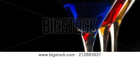 Colorful Cocktails in Martini Glasses on Black Background. Bar Commercials Concept.