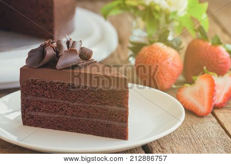 Triangle slices of delicious dark chocolate fudge cake decorated with chocolate curl on white plate put on wood table. Homemade bakery concept to present birthday cake party or cafe and restaurant. Delicious chocolate cake ready to served.