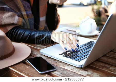 Female hands on laptop touch pad. Woman sitting with cup of coffee and cakes and working. Attractive model using computer with blank white copy space screen in cafe.
