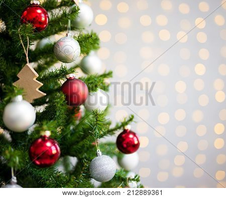 Christmas Background - Close Up Of Decorated Christmas Tree Over White Brick Wall With Lights