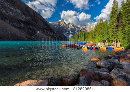 Sunrise at Moraine Lake with colorful canoes in Rocky Mountains, Banff National Park, Canada.