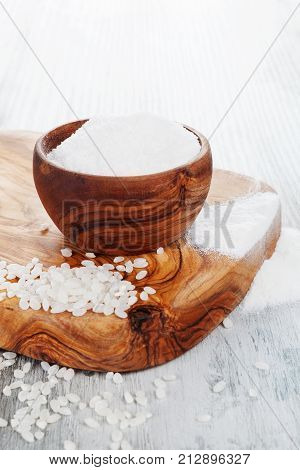 Rice flour in a wooden bowl rice on wooden chopping board. Gluten-free rice. Celiac flour.