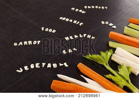 Vegetable soup ingredients. Broth bouillon soup rout vegetables and words made from alphabet noodles on dark surface. Menu soup gastronomy parsley carrot vegetable. Gastronomy background.