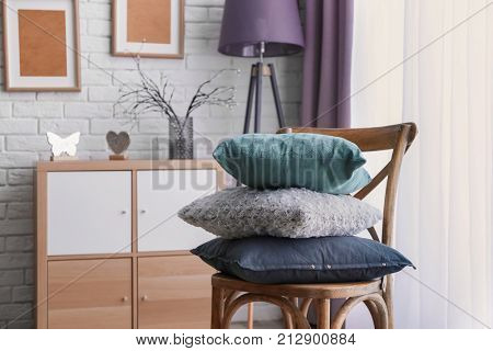 Room interior with chair and different pillows